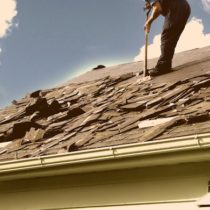 damaged roof with worker removing shingles
